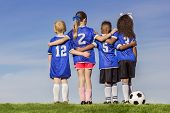 picture of little-league  - Diverse group of boys and girls soccer players standing together with a ball against a simple blue sky background - JPG