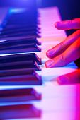 stock photo of soffit  - hands of musician playing keyboard in concert with shallow depth of field - JPG