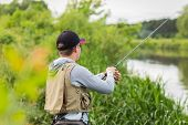 picture of trout fishing  - Fisherman on the river bank in sunglasses - JPG