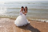 picture of married  - Happy couple just married relaxing on the beach laying in the ocean - JPG