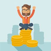 stock photo of winner man  - An overjoyed young hipster Caucasian man with beard sitting on the top of  coins - JPG