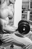 stock photo of dumbbell  - Strong and muscular guy with dumbbell - JPG