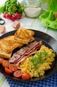 picture of scrambled eggs  - Scrambled eggs with bacon and French toast on a cast iron pan
