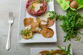 stock photo of tartar  - Beef tartar homemade potato chips sprinkled with parmesan shavings and microgreens - JPG