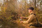 stock photo of fisherman  - Fisherman on the river bank - JPG