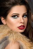 stock photo of straight jacket  - Closeup portrait of young beautiful brunette woman with cherry lips wearing fur jacket - JPG