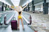 image of escalator  - Young woman wearing bikini with a suitcase walking to escalator at airport - JPG