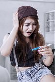pic of pregnancy test  - Portrait of unhappy teenage girls holding and looking at pregnancy test result - JPG