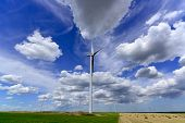 image of haystack  - windmill farm turbines with beautiful grey white clouds on green and haystack fields - JPG