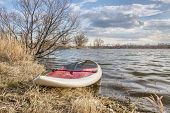 image of stand up  - stand up paddleboard with a paddle on alke shore - JPG