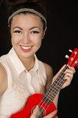 foto of ukulele  - Teen girl playing ukulele smiling at camera - JPG