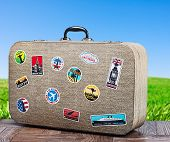picture of old suitcase  - old travel suitcase on background with grass field - JPG