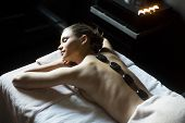foto of stone-therapy  - Young woman having a hot stone massage therapy - JPG