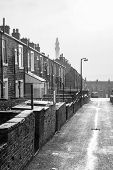 picture of victorian houses  - A rainy wet day in Yorkshire showing a typical Victorian terraced street leading towards a folly named Victorian Wainhouse Tower silhoutted by a misty sky. ** Note: Shallow depth of field - JPG