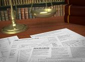 picture of income tax  - close up view of forms for usa taxes a scales and a library on background concept of taxes and laws  - JPG