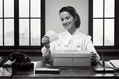 foto of shipping receiving  - Excited smiling woman receiving a gift box by mail with an envelope - JPG