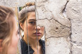 stock photo of reflections  - Teen girl looking at her reflection in the mirror fragments on the wall at street - JPG