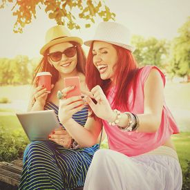 picture of takeaway  - Closeup outdoors shot of two young millennial women outdoors in park on sunny summer day with smart phone - JPG
