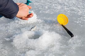 pic of ice fishing  - Winter fishing. Ice fishing. Fisherman on ice fishing from the well, a special winter fishing rod. Fishing in winter. Active, cold, fish, winter fishing tackle. Sport winter fishing/ ** Note: Soft Focus at 100%, best at smaller sizes - JPG