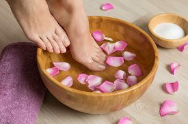 foto of foot  - Closeup shot of a woman feet dipped in water with petals in a wooden bowl - JPG