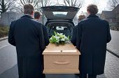 stock photo of coffin  - Bearers are carrying a coffin out of a mourning car - JPG