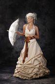 beautiful woman in wedding dress holding umbrella