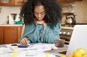 Single African-american Mother With Many Debts Feeling Stressed Calculating Finances, Siting At Kitc poster