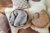 Wicker storage basket with woolen blanket inside, handbag and cushions on sheep carpet, top view fro poster