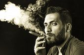 Постер, плакат: Man Smoking Cigar Surrounded By Smoke Short Bearded Man With A Gangster Look Smoking Cigar Surroun