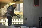 Worker Sandblasting a Residential Home