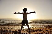 Silhouette of child on the beach, holding his hands up, hugging the sun