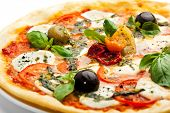Pizza with Mozzarella Cheese and Fresh Tomato and Pesto Sauce. Garnished with Dried Tomato, Green an