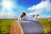 Girl relaxing on meadow, lying on the straw roll