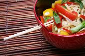 foto of thai food  - A colorful asian dish of noodles over a bamboo placemat - JPG