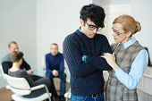 Portrait of mature female psychologist helping young man to overcome his fears and join  group thera poster
