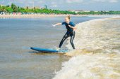Joyful Young Woman Beginner Surfer With Blue Surf Has Fun On Small Sea Waves. Active Family Lifestyl poster