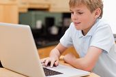 schöne junge mit einem Laptop in Küche