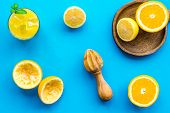Squeeze Fresh Oranges With Juicer. Orange Juice In Glass Near Half Cut Oranges On Blue Background To poster
