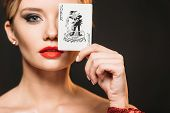 Attractive Girl With Makeup Covering Eye With Joker Card Isolated On Black poster