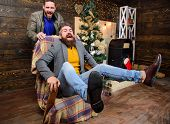 Best Friend Having Fun On Christmas Eve. Man Push Armchair With Friend. Cheerful Men Having Fun At H poster