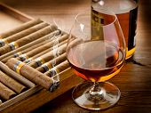 Cuban cigar and bottle of liquor on wood background