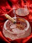 cuban cigar over ash tray and  and glass of liquor