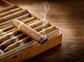 pic of cigar  - smoking cuban cigar over box  on wood background - JPG