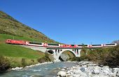 SWITZERLAND - SEP 16: Glacier Express of Matterhorn-Gotthard railway passing a bridge at Furka pass on September 16, 2012 in Switzerland.