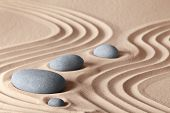 zen garden stones in row pattern in sand and rocks for relaxation and concentration during meditation