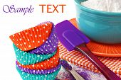 Colorful polka dot cupcake wrappers with color coordinated baking supplies on white background with