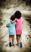 Two young girls in blue and pink dresses walking away with their backs turned