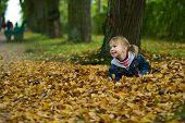 kleines Mädchen liegt am gelbe Blätter
