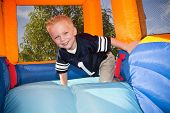 stock photo of yellow castle  - Boy playing on and inflatable Side - JPG