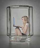 Blonde girl using a laptop computer in a glass container